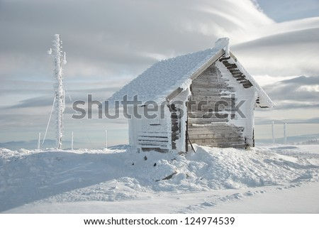 Small mountain shelter house and big antenna covered with lots of snow and icicles - stock photo