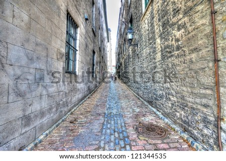 Small narrow street in Old Montreal, and in the background a man walking with his dog, HDR image - stock photo