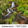 Small natural spring waterfall surrounded by moss and grass - stock photo