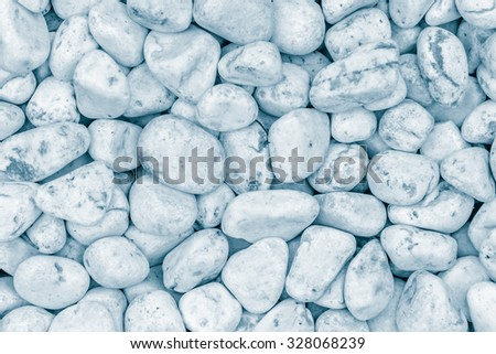 Small naturally polished white rock pebbles background in blue tone - stock photo
