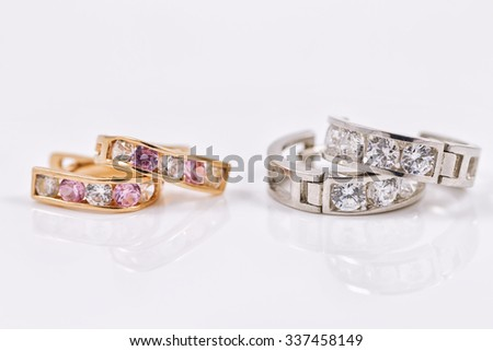 Small neat earrings in gold and silver on the reflecting surface - stock photo