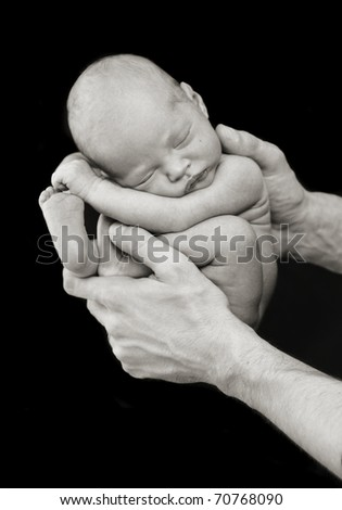Small newborn baby being held in her dad's hands - stock photo