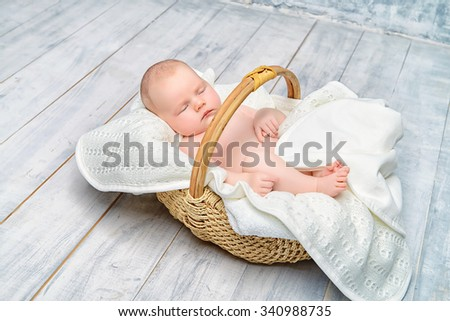 Small newborn baby sleeps in a basket on a white wooden floor. Provence style.  - stock photo
