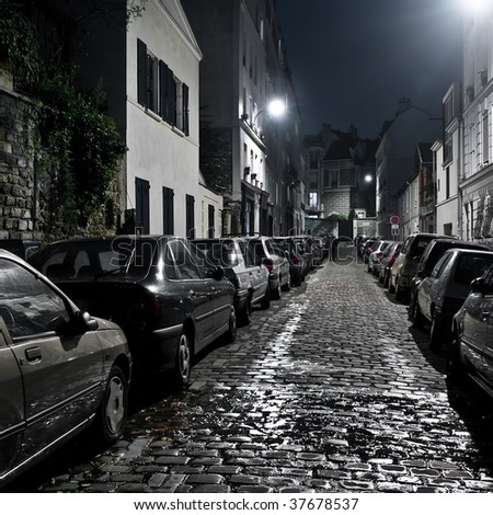 Small night street with car parking on Montmartre, Paris. - stock photo