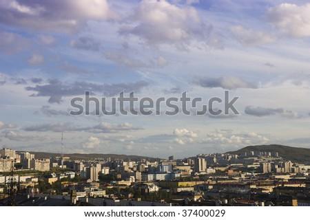 Small northern city among green hills - stock photo