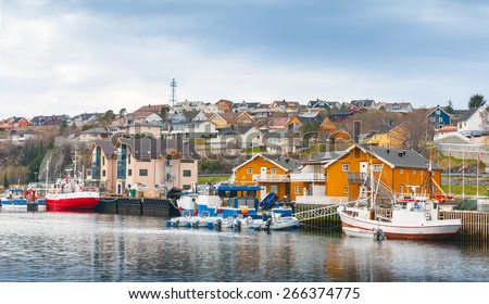 Small Norwegian fishing village, wooden houses and moored boats on the North sea coast  - stock photo