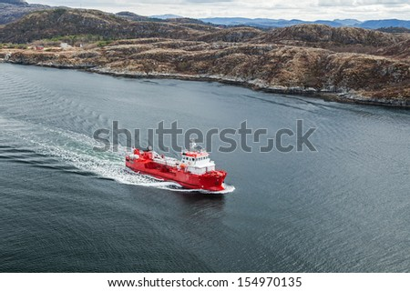 Small Norwegian red oil products tanker sails in the fjord - stock photo