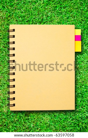 small notebook with memo bookmark pad isolated on green grass field