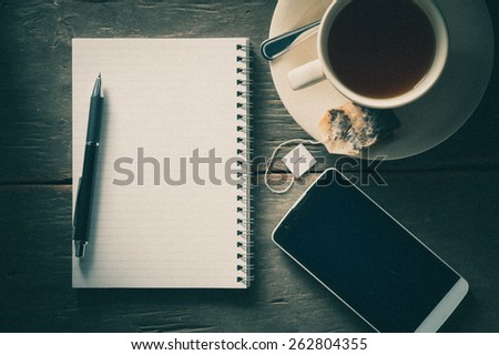 Small notepad with a cup of tea, pen, pencil and cellphone on rustic wood background with film filter effect - stock photo