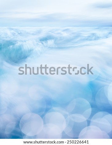 Small ocean waves with bokeh light patterns in the foreground.  This hi-key Image features a soft blurring effect. - stock photo