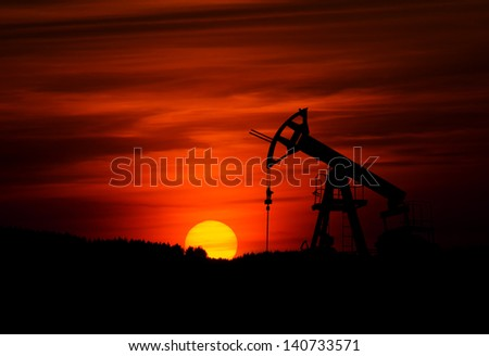 Small oil pump during sunset - stock photo