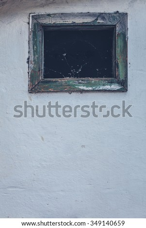 Small old dusty wooden window of an abandoned house - stock photo