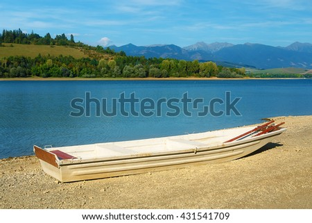 Small old fishing boat on a lake shore. - stock photo