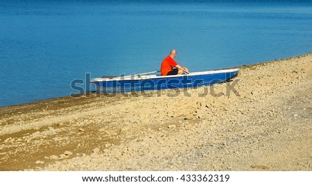 Small old fishing boat on a lake shore and man - stock photo