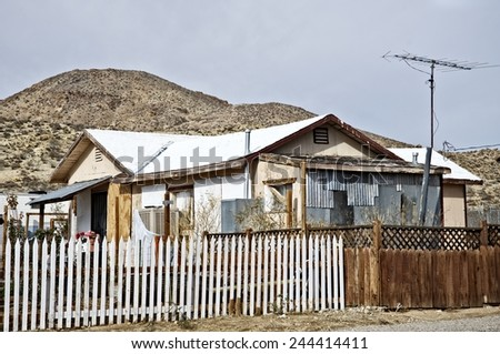 Small old house in Central California with a fence outside - stock photo