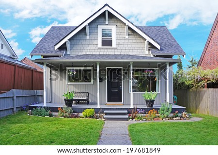 Small old house with entrance porch decorated with antique bench. Front yard has lawn and flower beds - stock photo