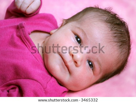 small one week old newborn baby on a pink background looking at camera - stock photo