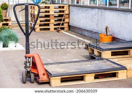Small orange forklift parked at a warehouse used to move, raise stack and load wooden pallets for storage, distribution and delivery - stock photo
