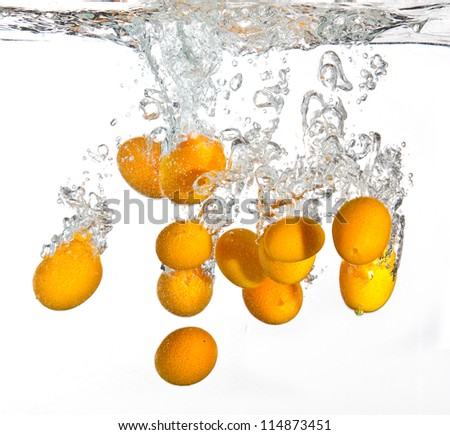 Small oranges falling into water causing a splash - stock photo