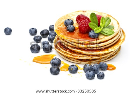 small pancakes topped with honey, raspberries and bilberries - stock photo