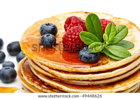 Small pancakes topped with honey, raspberries and bilberries on white background - stock photo