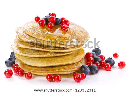 Small pancakes topped with honey, red currants and bilberries on white background - stock photo