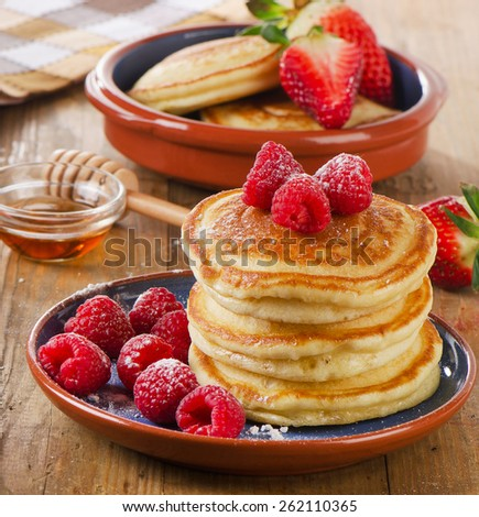 Small pancakes with fresh raspberries and  butter . Selective focus