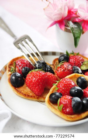 Small pancakes with raspberries and bilberries - stock photo