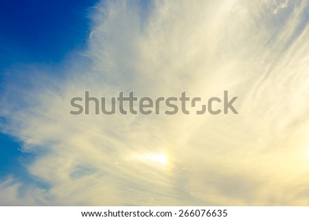 Small partially rainbow in a clouds on blue sky - stock photo