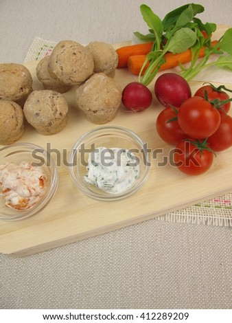 Small party rolls, cherry tomatoes, red radishes, carrots and dipping sauce - stock photo