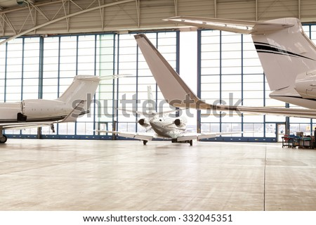Small Passenger Airplane Leaving Brightly Lit Hangar Through Opening Glass Doors with View Past Tails of Aircraft at Airport - stock photo