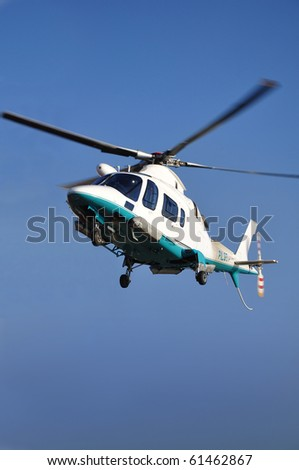 Small passenger helicopter hovering on blue sky. - stock photo