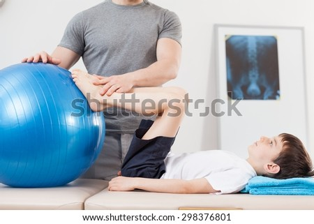Small patient doing exercise with fitness ball - stock photo