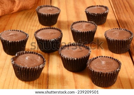 Small peanut butter cups on a rustic wooden table - stock photo
