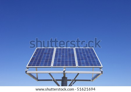 small photovoltaic panel against a clear blue sky - stock photo