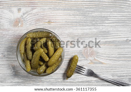 Small pickled cucumbers in bowl on old wooden table, top view