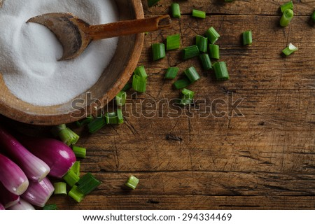 Small pieces of onion near old wooden salt box, retro background - stock photo