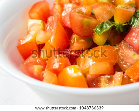Small pieces of tomatoes with some leaves of fresh basil in a small white bowl