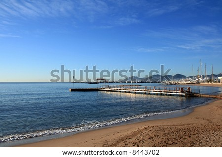 Small pier by the shore of the Mediterranean Sea in Cannes, French Riviera. - stock photo