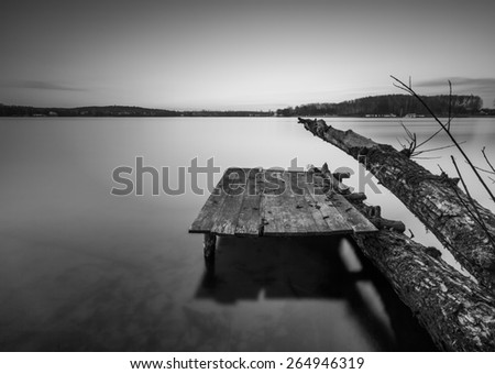 Small pier on lake, long exposure photo. Mazury lake district. Black and white photo - stock photo