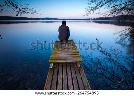 Small pier on lake with man silhouette. Mazury lake district.  - stock photo