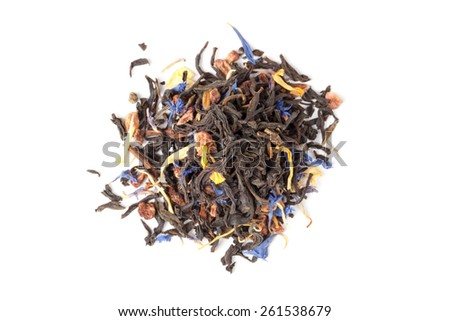 Small pile of big leaf black tea mixed with herbs and dry fruits. Calendula, sunflower, cornflower, rosehip berries. Top view, selective focus - stock photo