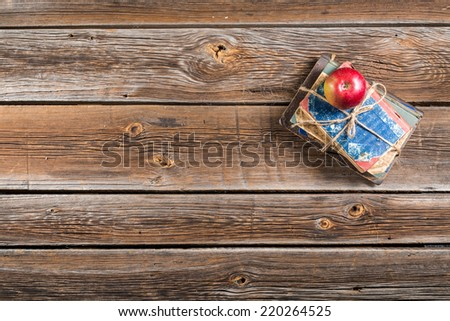 Small pile of books and apple on school desk - stock photo