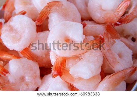 small pile of frozen shrimp closeup with tails - stock photo