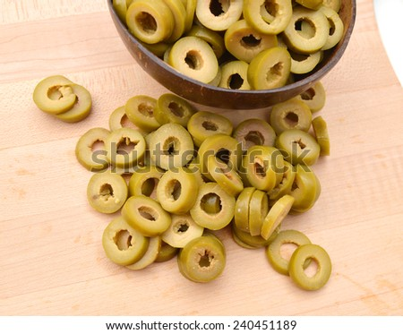 Small pile of sliced green olives isolated in wooden bowl on wooden board  - stock photo