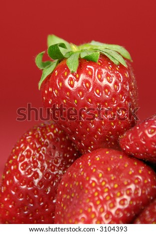 Small pile of strawberries set against red background SDOF