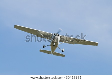 Small plane flying overhead against a blue sky - stock photo