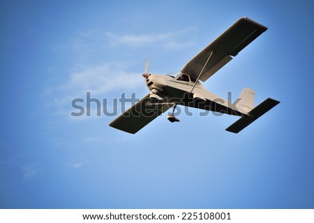 Small plane in the air. Blue sky with white clouds. - stock photo