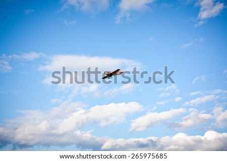 small plane in the sky with clouds - stock photo