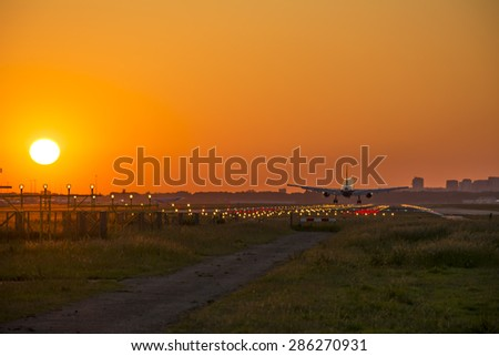 Small plane landing at dusk - stock photo